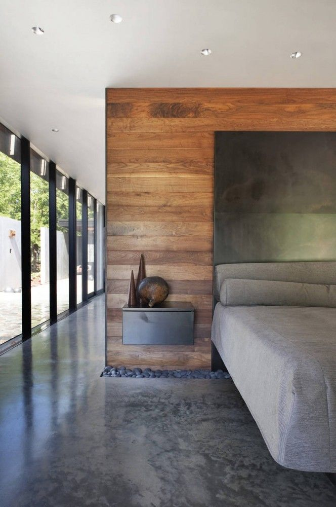 Masculine Bedroom With a Wood Wall and Polished Concrete Floor