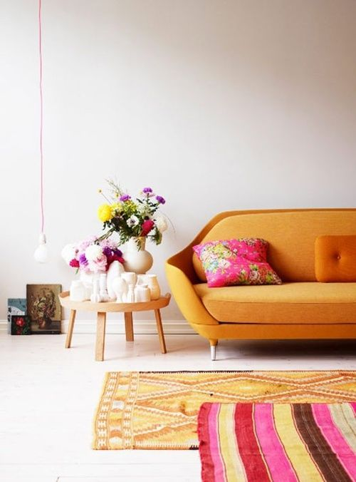 Mod Orange Couch with Funky Rugs